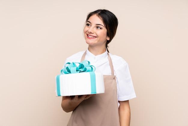 Chef de pastelaria mulher segurando um bolo grande sobre parede isolada, olhando para cima enquanto sorrindo Foto Premium