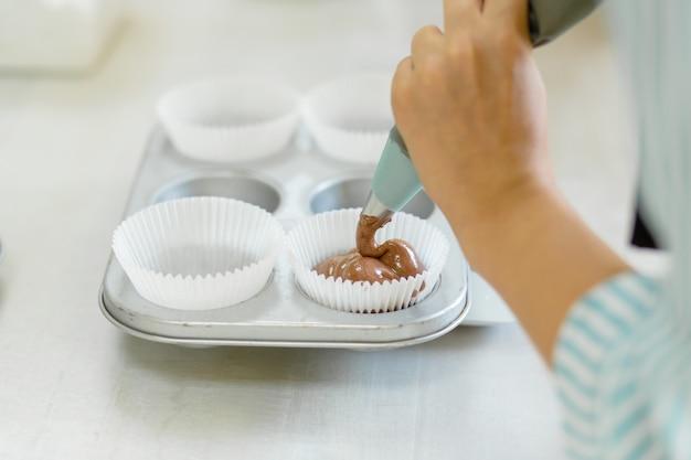 Chef de pastelaria profissional mulher espalha massa de chocolate na assadeira Foto Premium