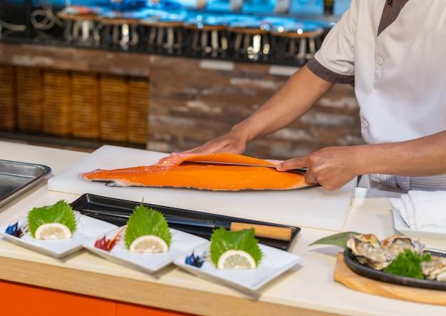 Chef de salmão de corte para sashimi, comida japonesa Foto Premium