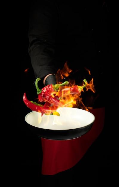 Chef de uniforme preto segura uma panela redonda e vomita pimenta vermelha e verde em um fogo ardente Foto Premium