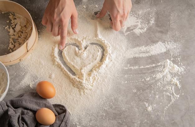 Chef, desenhando um coração em farinha Foto Premium