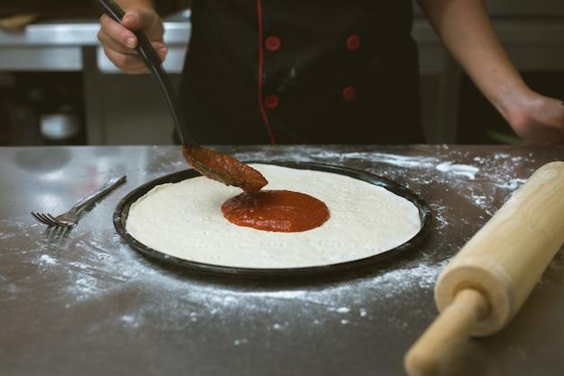 Chef fazendo pizza na cozinha Foto gratuita