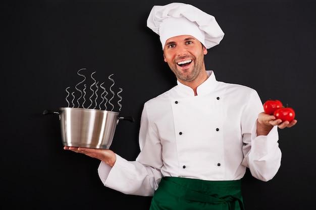 Chef feliz recomendando sopa de tomate Foto gratuita