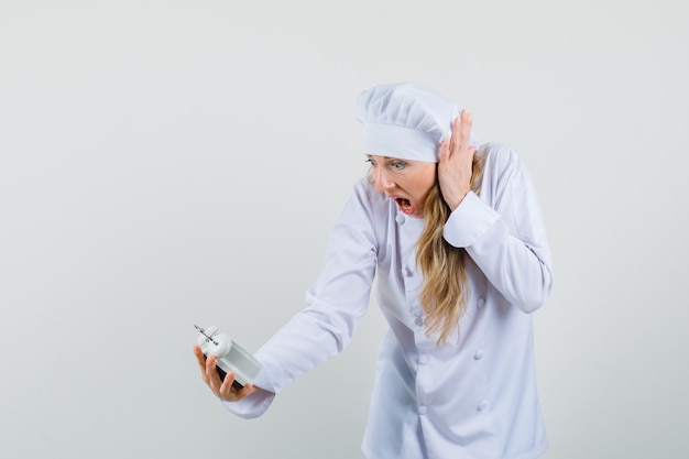 Chef feminina de uniforme branco olhando para o despertador e parecendo agitada Foto gratuita
