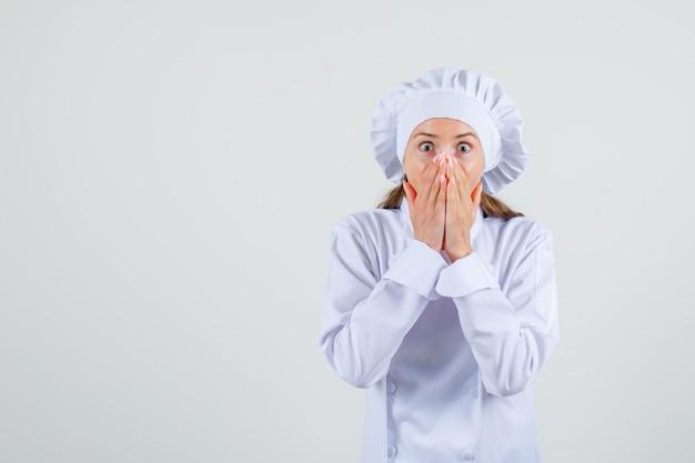 Chef feminino cobrindo a boca com as mãos em uniforme branco e parecendo assustado. vista frontal. Foto gratuita