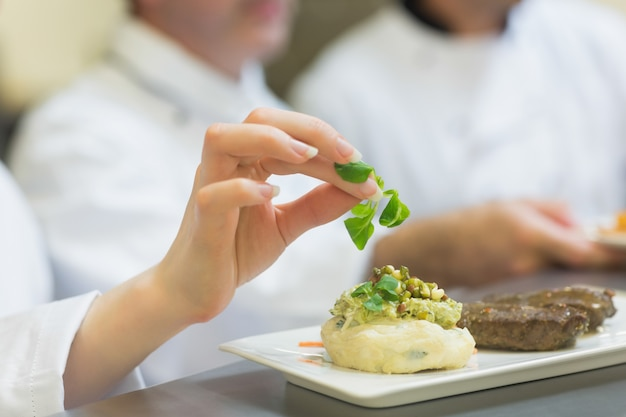 Chef feminino enfeitando um prato com bife Foto Premium