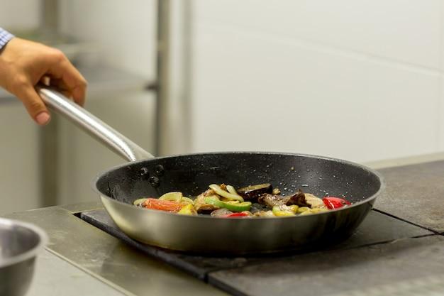 Chef fritar legumes no fogão a gás com fogo na cozinha Foto Premium