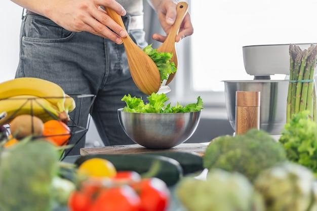 Chef jovem cozinhar salada saudável Foto Premium