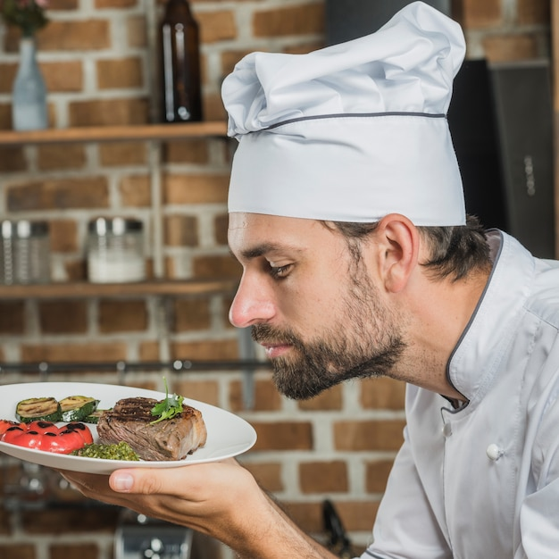 Chef masculino, cheirando o delicioso prato preparado Foto gratuita