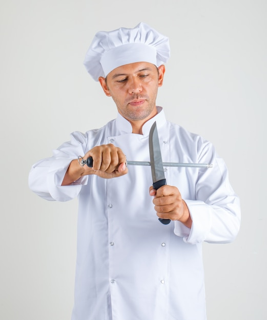 Chef masculino cozinhar de uniforme e chapéu segurando facas de cozinha e olhar confiante Foto gratuita