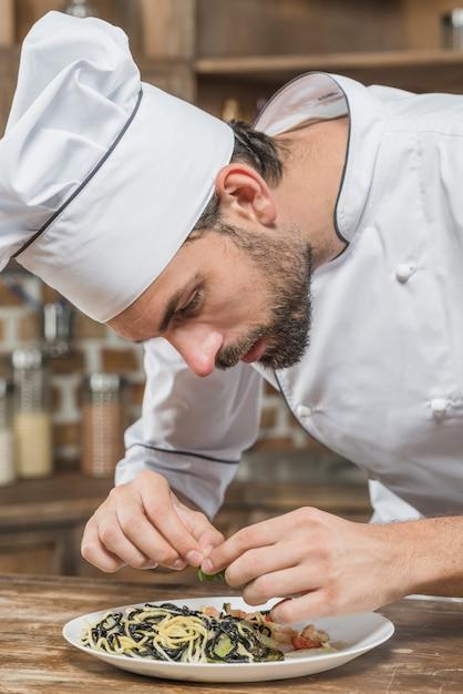 Chef masculino decorar macarrão no balcão da cozinha Foto gratuita