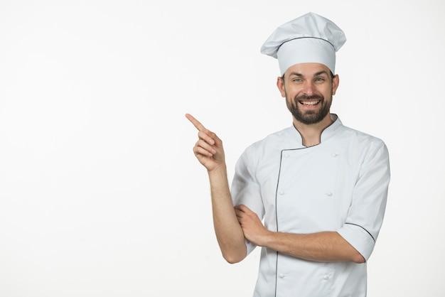 Chef masculino feliz apontando o dedo para algo isolado no fundo branco Foto gratuita