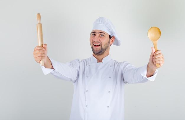 Chef masculino segurando uma colher de pau e um rolo de massa em uniforme branco e parecendo alegre Foto gratuita