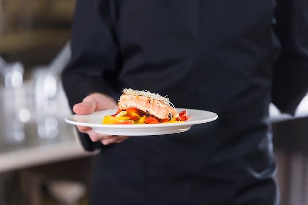 Chef mostrando seu prato Foto gratuita