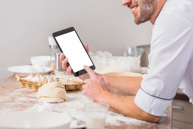 Chef na cozinha com modelo de tela do tablet Foto gratuita