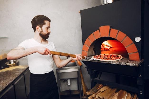 Chef na cozinha prepara pizza Foto gratuita