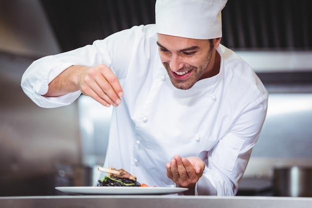 Chef polvilhar especiarias no prato Foto Premium