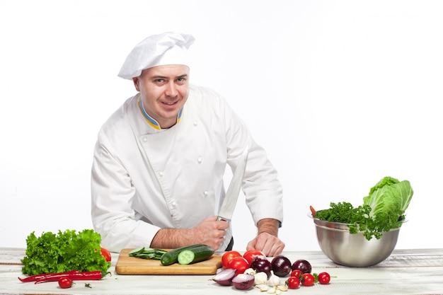 Chef posando com faca em sua cozinha Foto gratuita