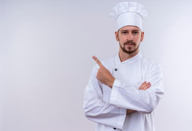 Chef profissional cozinheiro em uniforme branco e chapéu de cozinheiro apontando para o lado com o dedo indicador, parecendo confiante em pé sobre um fundo branco Foto gratuita