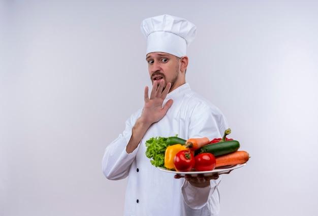 Chef profissional cozinheiro em uniforme branco e chapéu de cozinheiro segurando um prato com legumes, fazendo gesto de defesa com a mão em pé sobre o fundo branco Foto gratuita