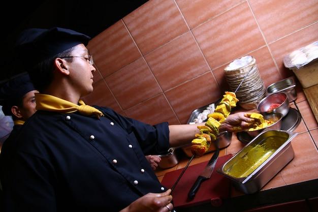 Chef profissional homem fazendo carne Foto gratuita