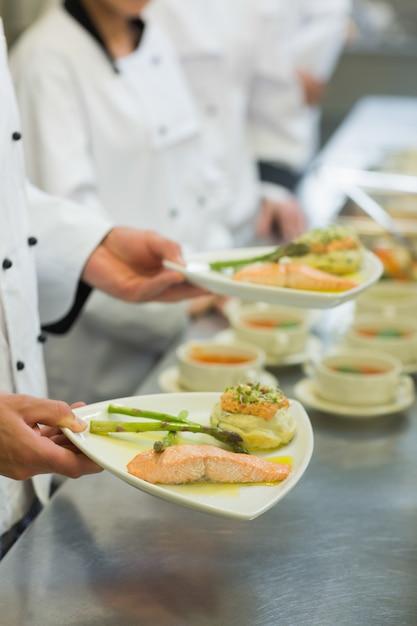 Chef que prende o prato do salmão Foto Premium