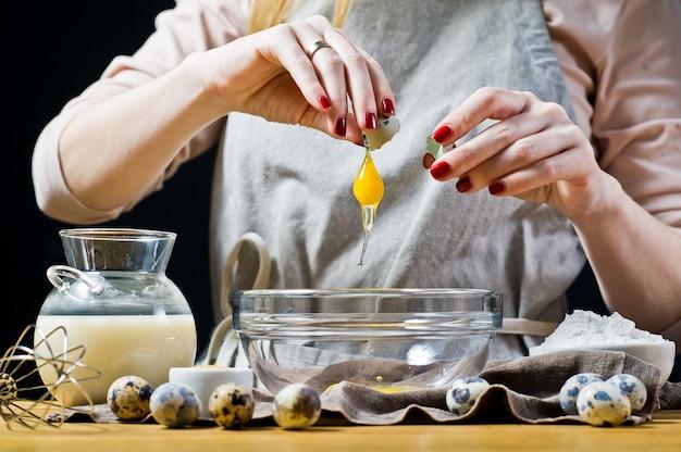 Chef quebra ovos de codorna em uma tigela. Foto Premium