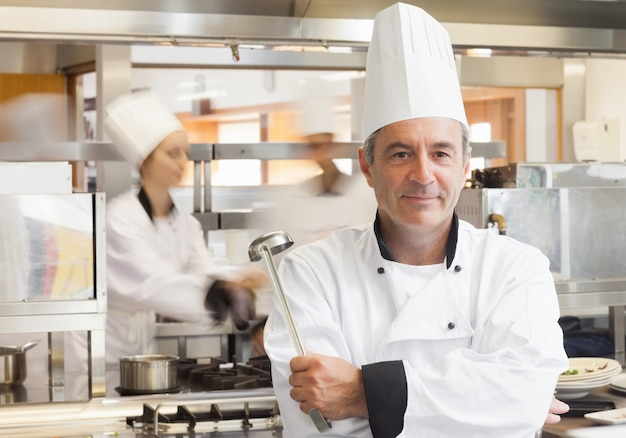 Chef segurando a concha enquanto sorrindo Foto Premium