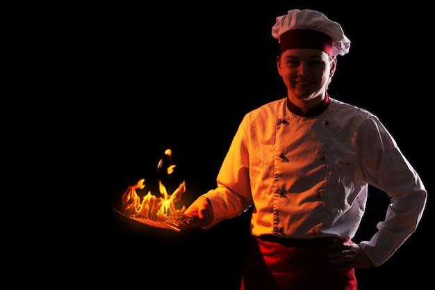 Chef segurando a panela com fogo dentro Foto gratuita