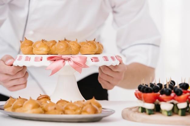 Chef segurando a placa com merengue inflamado Foto gratuita