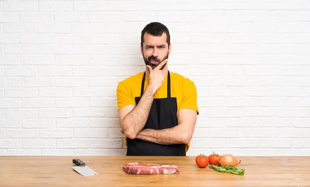 Chef segurando em um pensamento de cozinha Foto Premium