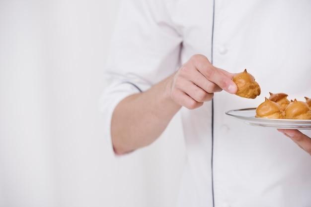 Chef segurando o prato de merengue Foto gratuita