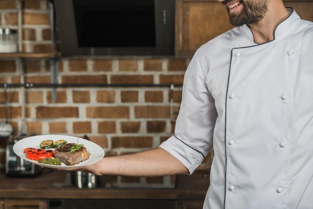 Chef segurando prato preparado para servir no restaurante Foto gratuita