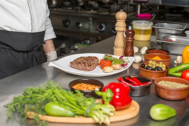 Chef servido cogumelo bife, salada de rúcula e tomate Foto gratuita