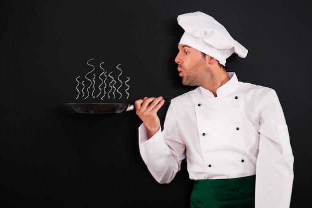 Chef soprando fumaça da panela Foto gratuita