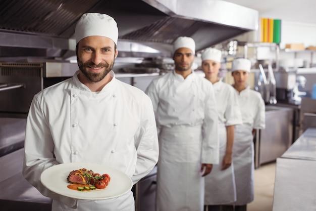 Chef sorridente segurando um prato delicioso na cozinha Foto Premium