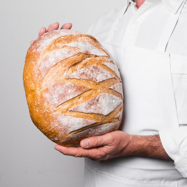 Chef, vestindo roupas brancas, segurando um pão quente Foto gratuita