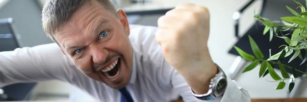 Chefe louco grita ameaça com um punho e olha Foto Premium