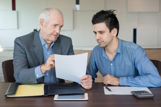 Chefe sério que explica o documento ao colega Foto Premium