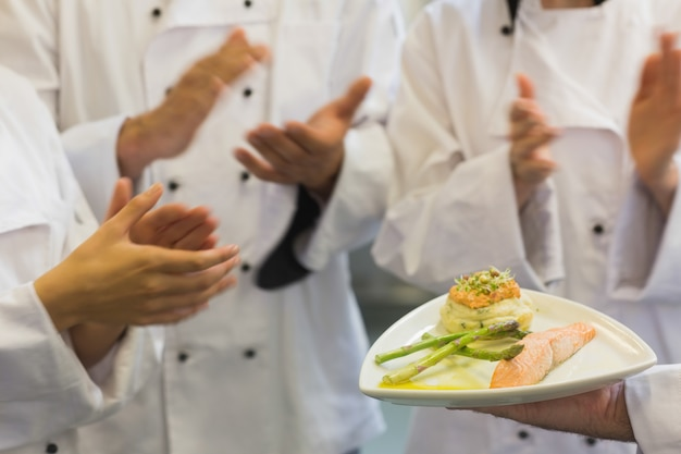 Chefs aplaudindo um prato de salmão Foto Premium
