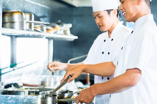 Chefs asiáticos cozinhar no restaurante Foto Premium