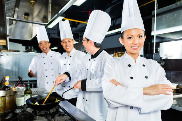 Chefs asiáticos na cozinha do restaurante do hotel Foto Premium
