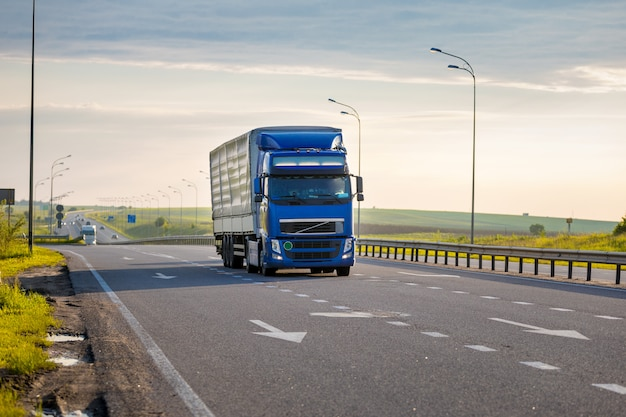 Chegando caminhão azul na estrada em uma paisagem rural ao pôr do sol Foto Premium