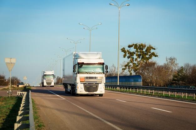 Chegando caminhão vermelho na estrada em uma paisagem rural ao pôr do sol Foto Premium