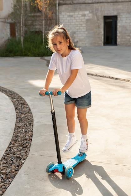 Cheio, tiro, de, menina, montando, scooter Foto gratuita