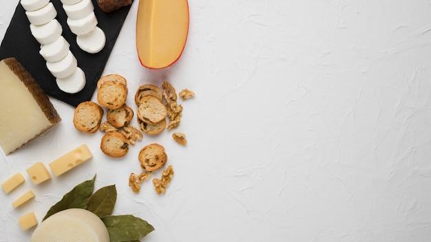 Chesses frescos com fatia de pão e noz sobre a superfície de concreto Foto gratuita