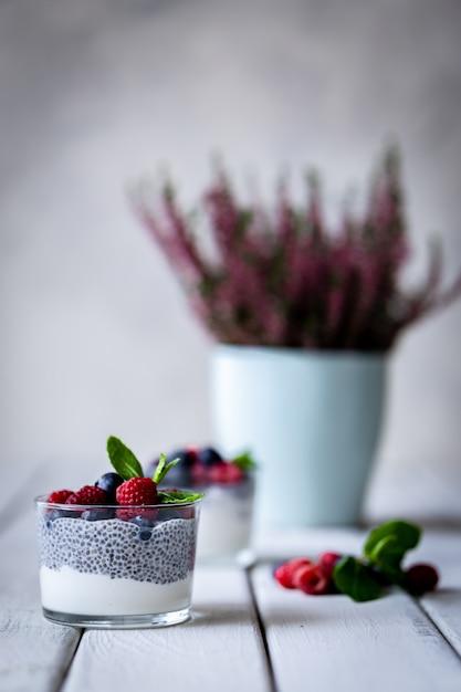 Chia com frutos silvestres. framboesas e mirtilos. sobremesa deliciosa e saudável e flores violetas sobre uma mesa rústica de madeira branca. Foto Premium