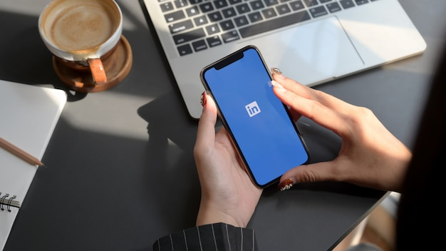 Chiang mai, tailândia - 31 de janeiro de 2020: fêmea segurando o iphone com a tela do linkedin. o linkedin ajuda a criar um currículo e procurar um novo emprego Foto Premium
