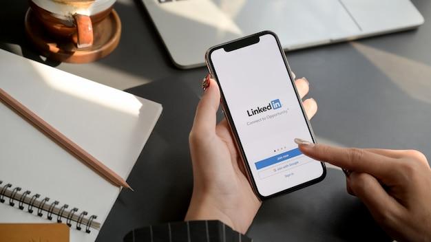 Chiang mai, tailândia - 31 de janeiro de 2020: fêmea tocando iphone com tela do linkedin. o linkedin ajuda a criar um currículo e procurar um novo emprego Foto Premium