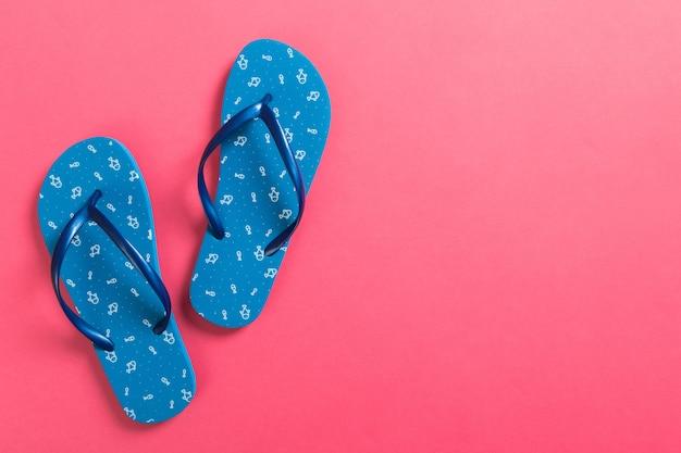 Chinelos azuis em fundo rosa. vista superior com espaço de cópia Foto Premium
